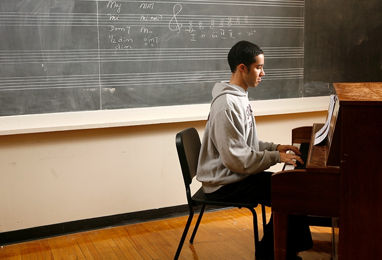 A student playing a piano in one of the practice rooms in Corthell Hall on our Gorham campus.