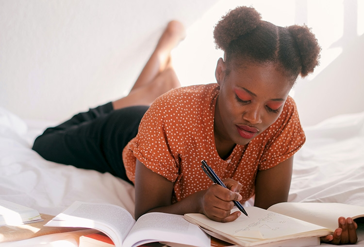 A student studying with a pen, a notebook, and several textbooks, while laying on her stomach.