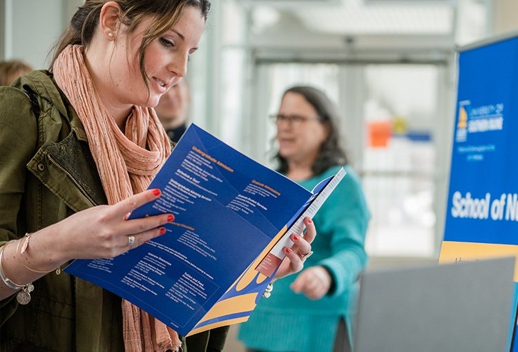 A student reviewing program information at an open house