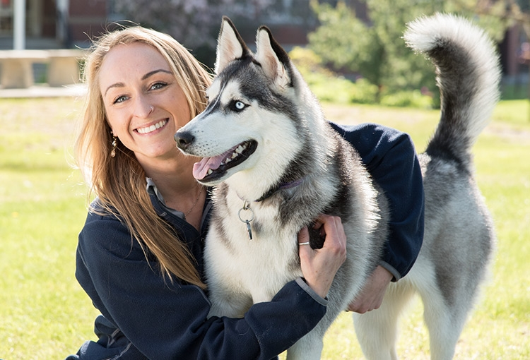 A student hugging a husky on the Gorham campus green.