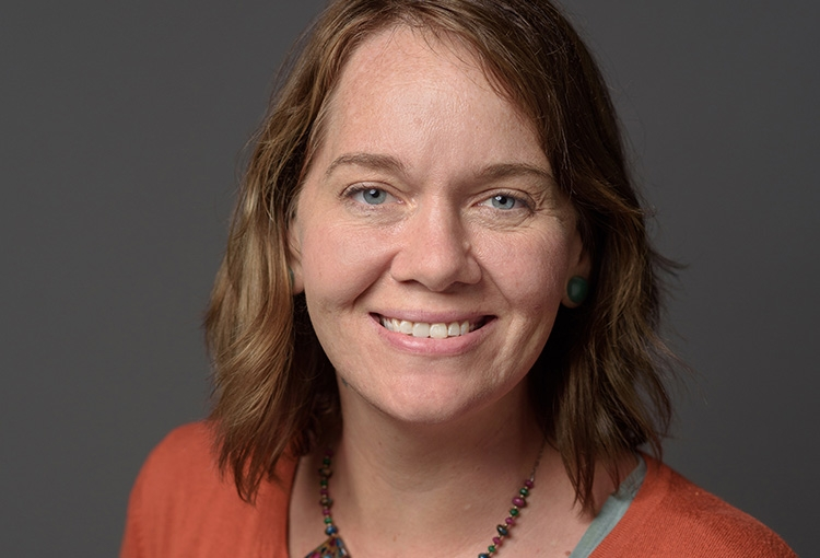 Assistant professor Heather Shattuck-Heidorn wearing a brick-red cardigan sweater, a statement necklace, and teal circle earrings.