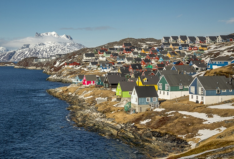 Colorful houses in Greenland's capital city of Nuuk overlook the ocean. Snow covered mountains crowd the horizon.