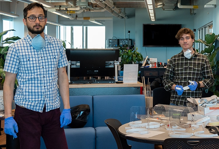 Dr. Asheesh Lanba and Berkeley Elias in our MIST Lab with their face shield prototypes displayed on a table that sits between them. Both men are wearing blue latex gloves and have face masks hanging around their necks.