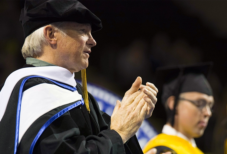 David E. Shaw clapping in a cap and gown at Commencement 2015. A student stands clapping to his left.