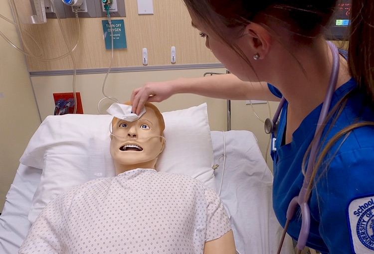 A Nursing student treating a mannequin in the Simulation lab
