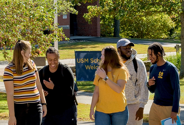 A group of students walking on our Gorham campus on a sunny autumn day.