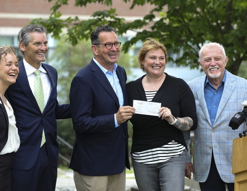 A photo of Reid and Dan Crewe presenting UMS Chancellor Dannel Malloy with a $2 million check