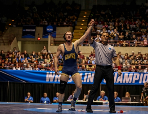 Photo of Dan Del Gallo getting his arm raised by a referee after winning the NCAA Division III Wrestling National Championship in the 149 pound weight class