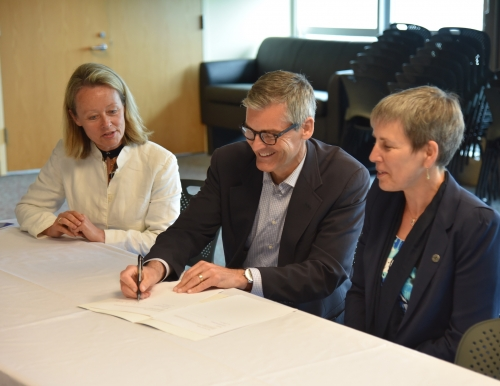 USM President Glenn Cummings signs agreement with Sigrid Ag and Aase Tveito of the University of Tromsø