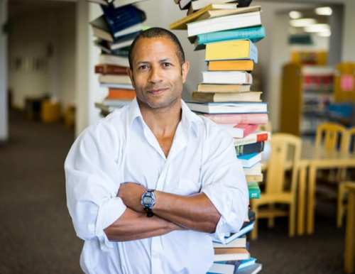 JJ Amaworo Wilson in front of a stack of books