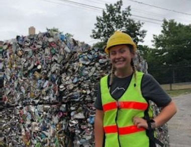 student stands near recycling