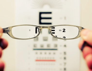 Glasses held in front of eye exam chart.