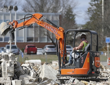 A photo of a small excavator picking cinder blocks
