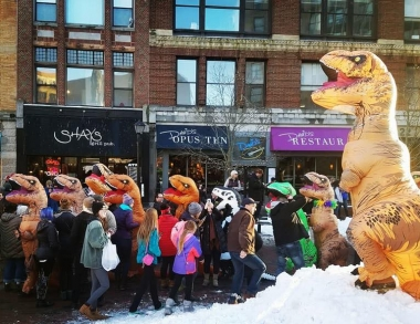 A T-rex beckons to a crowd in Monument Square on Jan. 20, 2018
