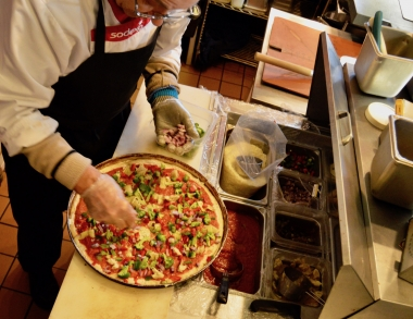 A food service worker makes a pizza at the Woodbury Campus Center