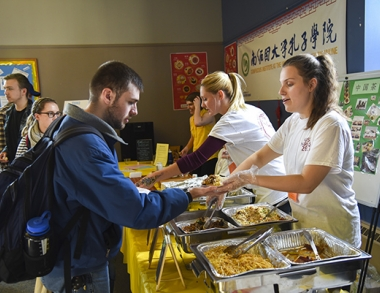 Students serving food at the 5th Annual Husky Harvest