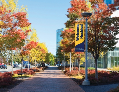 A campus walkway with brightly colored autumn trees and a banner that reads Welcome Huskies.