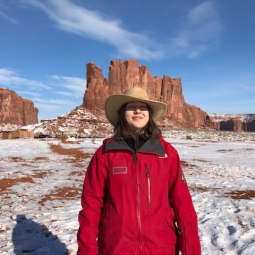 Picture of Kristina, standing in the desert. There is some light snow on the ground.