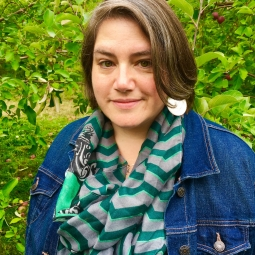 Sarah Holmes wearing a green and grey scarf and a blue denim jacket