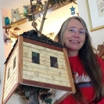 Portrait of Amy Hagberg holding outside-in house sculpture