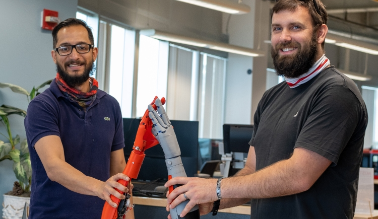 Assistant professor Asheesh Lanba and electrical engineering major Adam Robert high-five using prosthetic arm prototypes they developed in our MIST lab.